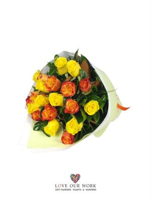 A lovely, lush bouquet of long stem yellow and orange roses teamed with glossy foliage